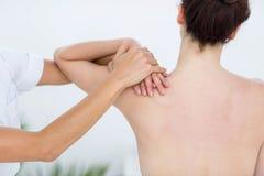Fisioterapista che fa massaggio della spalla Fotografia Stock