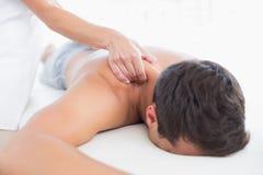 Fisioterapista che fa massaggio della spalla al suo paziente Fotografia Stock
