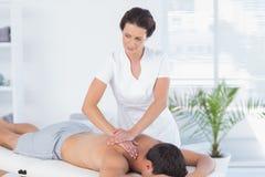 Fisioterapista che fa massaggio della spalla al suo paziente Fotografia Stock Libera da Diritti