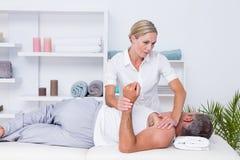 Fisioterapista che fa massaggio della spalla al suo paziente immagine stock libera da diritti