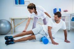 Fisioterapista che fa terapia della gamba ad un uomo che usando il rotolo di schiuma Fotografia Stock