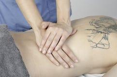 Fisioterapista che fa una parte posteriore della ragazza di massaggio allungamento Fotografia Stock