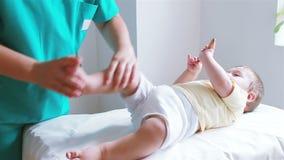 Fisioterapista che massaggia il piccolo piede del neonato video d archivio