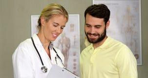 Fisioterapista che mostra perizia medica al paziente stock footage