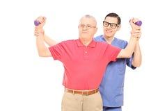 Fisioterapista che mostra un esercizio all'uomo maturo Immagini Stock Libere da Diritti