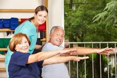 Fisioterapista con fare degli anziani Immagini Stock