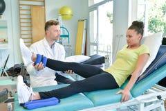 Fisioterapista del maschio adulto che cura il paziente della femmina della gamba Fotografia Stock