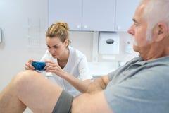 Fisioterapista femminile che prende a pazienti dell'immagine gamba Immagine Stock