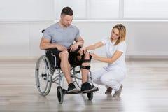 Fisioterapista femminile Fixing Knee Braces sulla gamba del ` s dell'uomo immagine stock libera da diritti