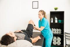 Fisioterapista Helping Male Athlete con l'esercizio di gamba fotografia stock libera da diritti