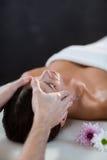 Fisioterapista maschio che dà massaggio capo al paziente femminile Fotografia Stock