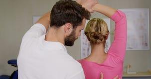 Fisioterapista maschio che dà massaggio del braccio al paziente femminile archivi video