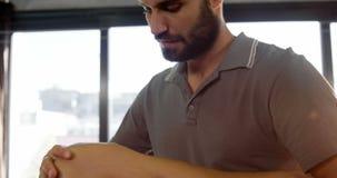 Fisioterapista maschio che dà massaggio del ginocchio al paziente femminile archivi video