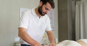 Fisioterapista maschio che dà massaggio della gamba al paziente femminile stock footage