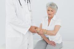 Fisioterapista maschio che esamina il polso di una donna senior fotografie stock