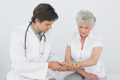 Fisioterapista maschio che esamina il polso di una donna senior immagini stock
