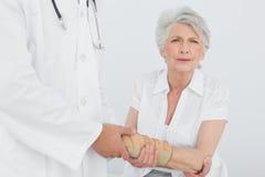 Fisioterapista maschio che esamina il polso di una donna senior fotografia stock libera da diritti