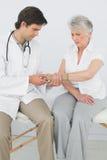 Fisioterapista maschio che esamina il polso di una donna senior fotografie stock libere da diritti