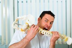 Fisioterapista nella sua clinica che è pazzo pungente Immagini Stock Libere da Diritti