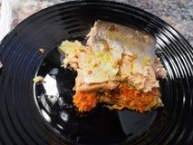 Fisk med morötter på en svart platta, bakad fisk på en svart platta Ett stadigt fullt skott av en fisk och ett morotmål som hälls royaltyfria foton