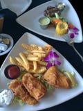 Fisk och chiper med biff och grönsakplattan royaltyfria bilder