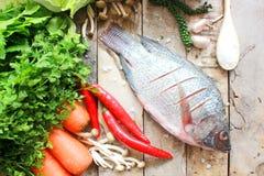Fisk och grönsak på träbräde Arkivbild