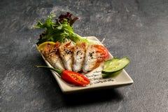 Fisk på en vit platta med röd peppar och grön sallad Royaltyfria Foton