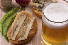 Fisk på rostat bröd och ljust öl Fotografering för Bildbyråer