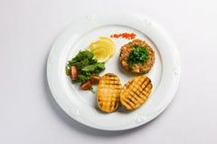 Fisk som är tartare med grönsaker och smällare Royaltyfri Fotografi