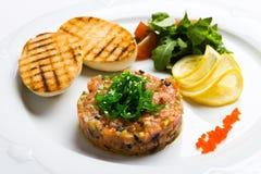 Fisk som är tartare med grönsaker och smällare Fotografering för Bildbyråer