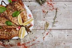 Fisk som lagas mat på gallret i restaurangen på en träbakgrund Arkivbilder