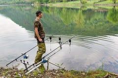 Fiska affärsföretag, karpfiske Fiskaren med grön rubber lårhöjdpunkt startar för fiska och kamouflageskjorta arkivbild