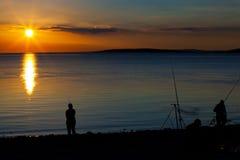 Fiska för flundra på solnedgången på kusten Royaltyfri Foto