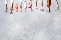 Fiska krokar och beten i en uppsättning för att fånga den olika fisken på en grå bakgrund med kopieringsutrymme Lekmanna- l?genhe arkivbilder