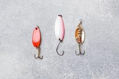 Fiska krokar och beten i en uppsättning för att fånga den olika fisken på en grå bakgrund med kopieringsutrymme Lekmanna- l?genhe royaltyfri bild