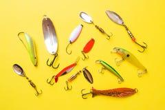 Fiska krokar och beten i en uppsättning för att fånga den olika fisken på en gul bakgrund med kopieringsutrymme Lekmanna- l?genhe arkivfoton