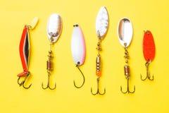 Fiska krokar och beten i en uppsättning för att fånga den olika fisken på en gul bakgrund med kopieringsutrymme Lekmanna- l?genhe fotografering för bildbyråer