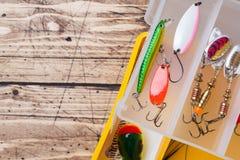 Fiska krokar och beten i en uppsättning för att fånga den olika fisken på en träbakgrund med kopieringsutrymme arkivbild
