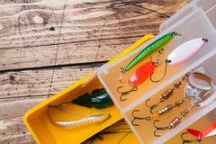 Fiska krokar och beten i en uppsättning för att fånga den olika fisken på en träbakgrund med kopieringsutrymme arkivbilder