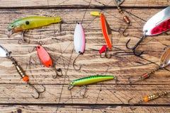 Fiska krokar och beten i en uppsättning för att fånga den olika fisken på en träbakgrund med kopieringsutrymme Lekmanna- l?genhet fotografering för bildbyråer