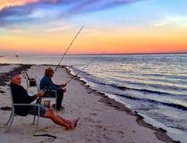 Fiska med en solnedgång Arkivbild