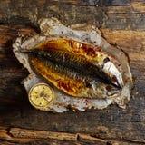 Fiska med limefrukt på pergamentpapper på en svart träbakgrund Top beskådar arkivbild