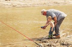 Fiska med morfadern på den leriga flodstranden Arkivfoton