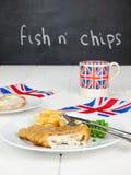 Fiska och chiper med en kopp tesmörgås- och unionjac Arkivbild
