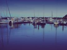 Fiska och segla fartyg som reflekterar i vatten i morgonsolljus royaltyfria bilder