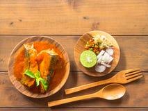 Fiska på burk i tomatsås med örtsallad Arkivfoto