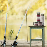 Fiska på floden En metspö och en termos med koppar i K Royaltyfri Fotografi