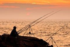 Fiska på solnedgången Arkivbild