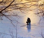 Fiska på den djupfrysta floden Arkivbild