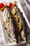 Fiska saury som grillas med citronen och gräslökar på en plattanärbild Ve arkivbild